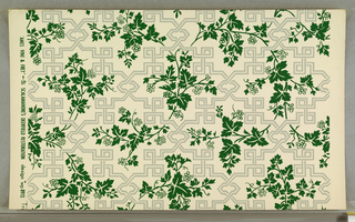 "On white ground, gray fret pattern with flat green vine, leaves, berries entwined. Printed in margin: ""AMES VINE and FRET...SCALAMANDRE'S DEERFIELD RESTORATION design No. 8912."""