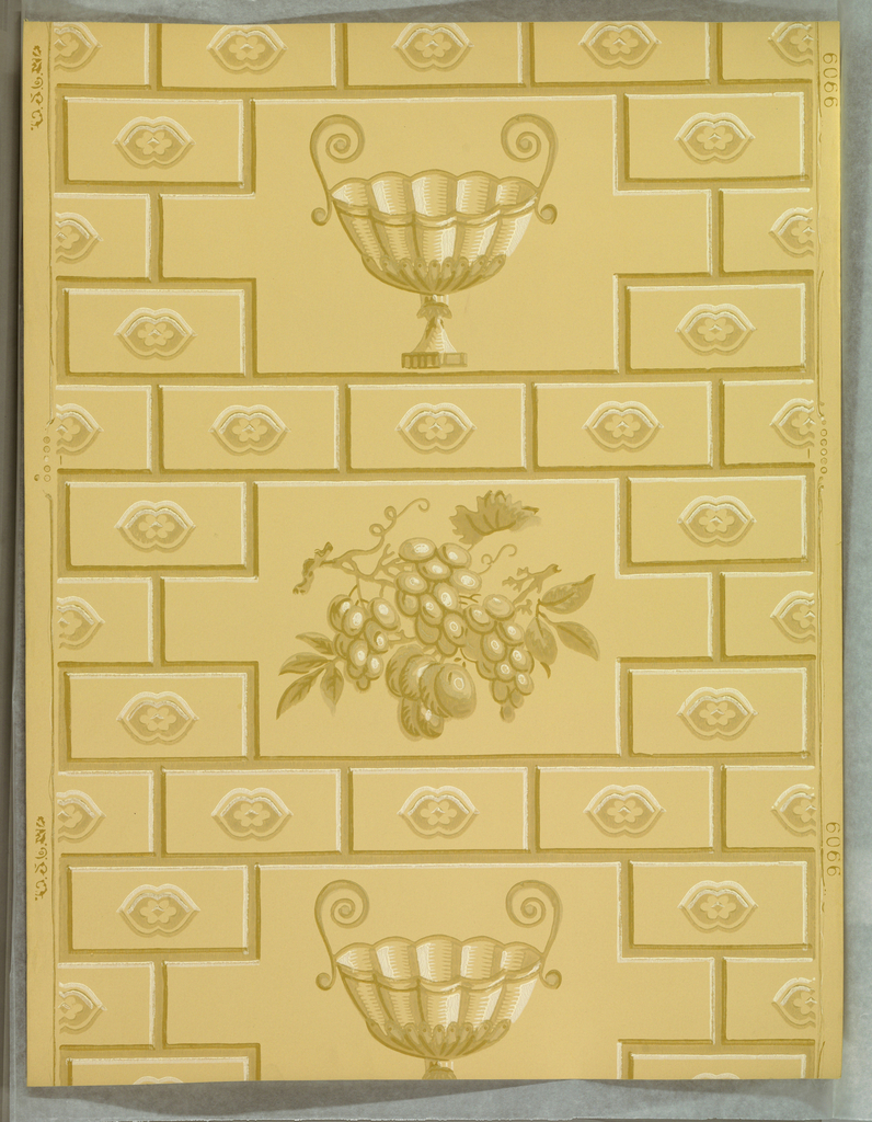 "a) On beige ground, rectangles arranged like building blocks or brick, each with a central motif with floral center. ""Block"" pattern interrupted by reserves with alternating two-handled epergne and bunch of grapes. b) duplicate, on pale green ground, with shades of green, red and white. Printed in selvedge""T S Co. (thistle) 9909"""