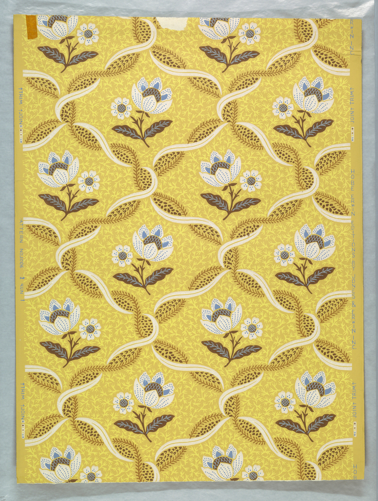 Trellis pattern created with intertwined ribbon and vine. A floral motif is placed within each frame. Printed in blue, brown, white, tan and yellow on a yellow ocher ground. Pattern #1006, produced by Hobe Erwin Editions, USA, 1970's.
