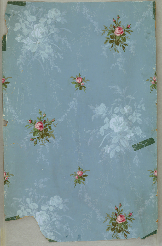 Realistically rendered red roses and rose buds, alternating large and small, on the diagonal. Secondary pattern of more subtle monochrome blue bouquets. also sublte monochrome blue swags connecting red roses. Printed on medium blue ground.