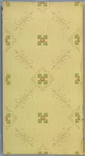 Grid or trellis pattern formed by Eastlake-like flourishes. A square medallion with pointy projections on four sides contains a quatrefoil composed of a flower and four leaves which sits at each intersection in fills the voids. Printed in green and brown on a moire-patterned yellowish background.