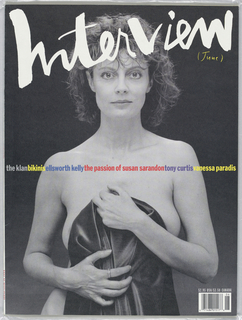 """Magazine cover of a black and white nude photograph of Susan Sarandon standing while holding a black cloth in front of her.  At the top """"Interview"""" written in white lettering."""