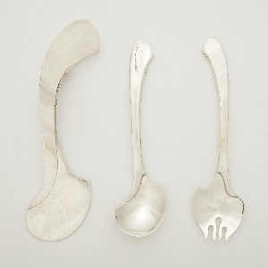 Fork with serpentine outline; flat curving stem with curved join to the broad head, with four asymmetrical central tines.