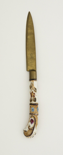 Leaf-shaped brass blade, brass ferrule. Pistol-shaped porcelain handle. Painted floral design in yellow, brown, blue, red and gold on a white ground.