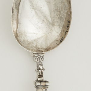 Three curved tines, short, rounded shoulders, decorative chiseling at the joint and neck. Hinged at the neck, locket engraved with floral pattern. Square handle with eagle on top.  Large oval-shaped spoon bowl with three rings on the back which can be slotted over the tines of the fork.