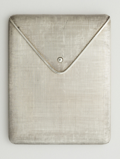 Flat, rectangular in shape, modeled in the form of an envelop or pouch, with triangualr flap and clasp overlapping upper edge, bottom edge hinged, opens to reveal hinged bar. Exterior silver textured, interior polished.