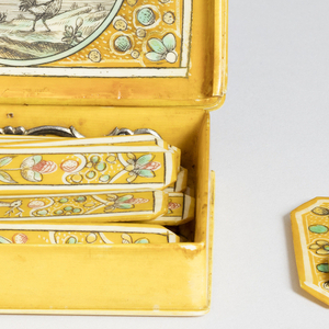 Game-counter box, rectangular, with yellow- and green-stained hinged cover showing female figure representing Africa, holding parasol and tambourine, seated on a lion-drawn chariot. Inside, game counters. One of a set of four boxes (1960-1-13-1a/v / 4a/v).