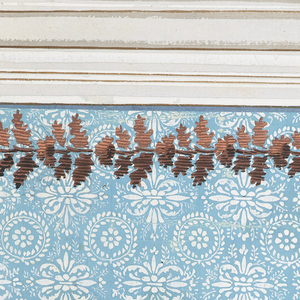 A dado is at the bottom, an entablature on top. The lower part of the design suggests horizontal rows of petal discs, with petals and palmettes in the wedges, for the panel. The upper part suggests alternate and staggered rows of naturalized fleur-de-lis leaves.