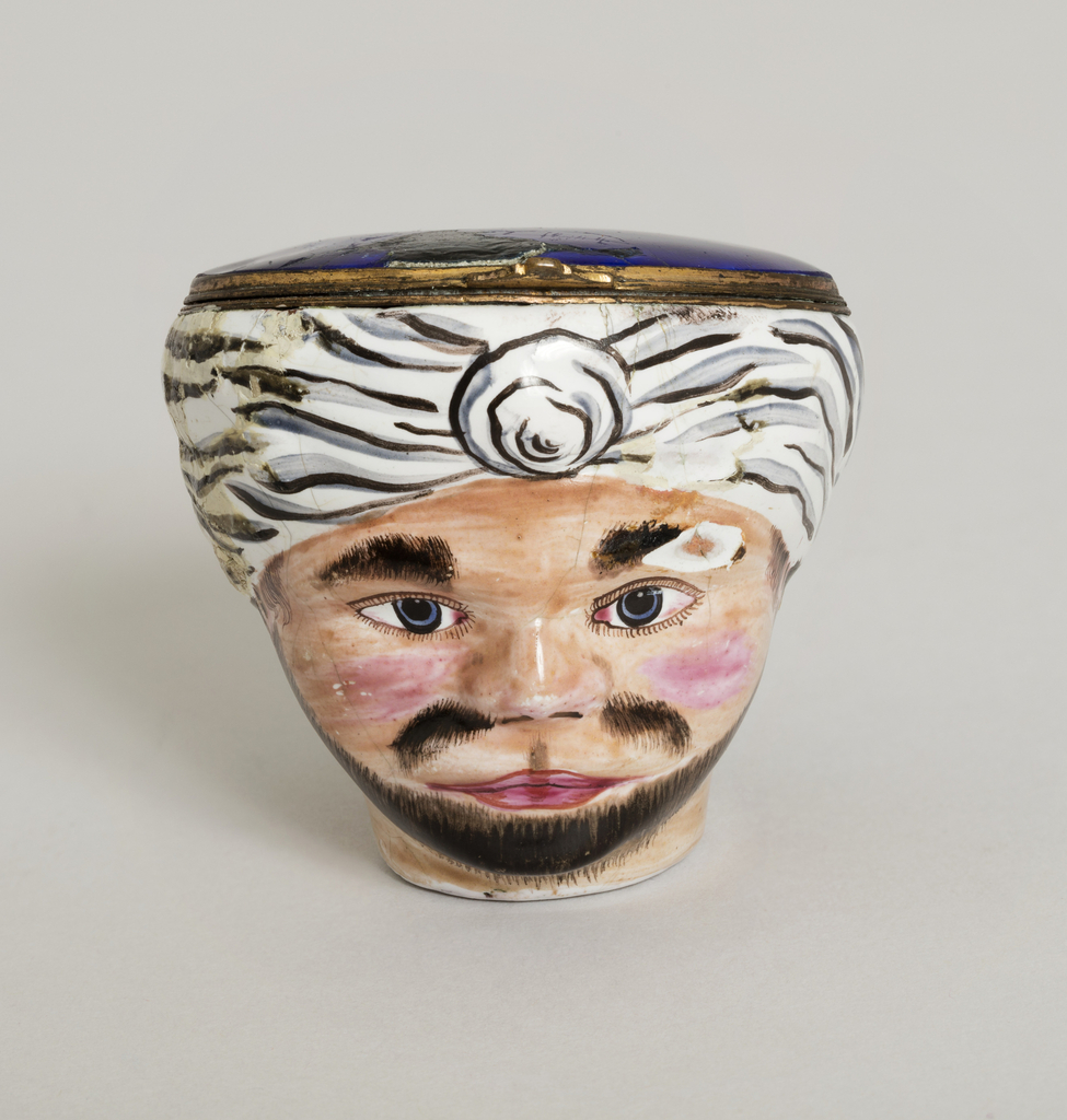 """In shape of a head; field of white enamel, with features colored.  Hinged lid and deep blue on outside.  Representation of a """"Turk."""""""