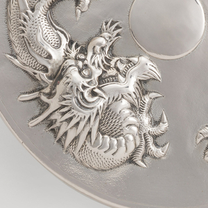 Circular mirror with bulbous handle, the back ornamented with repoussé decoration of a large Chinese dragon on a subtle hammered surface. (Part of set  1996-109-2/7).