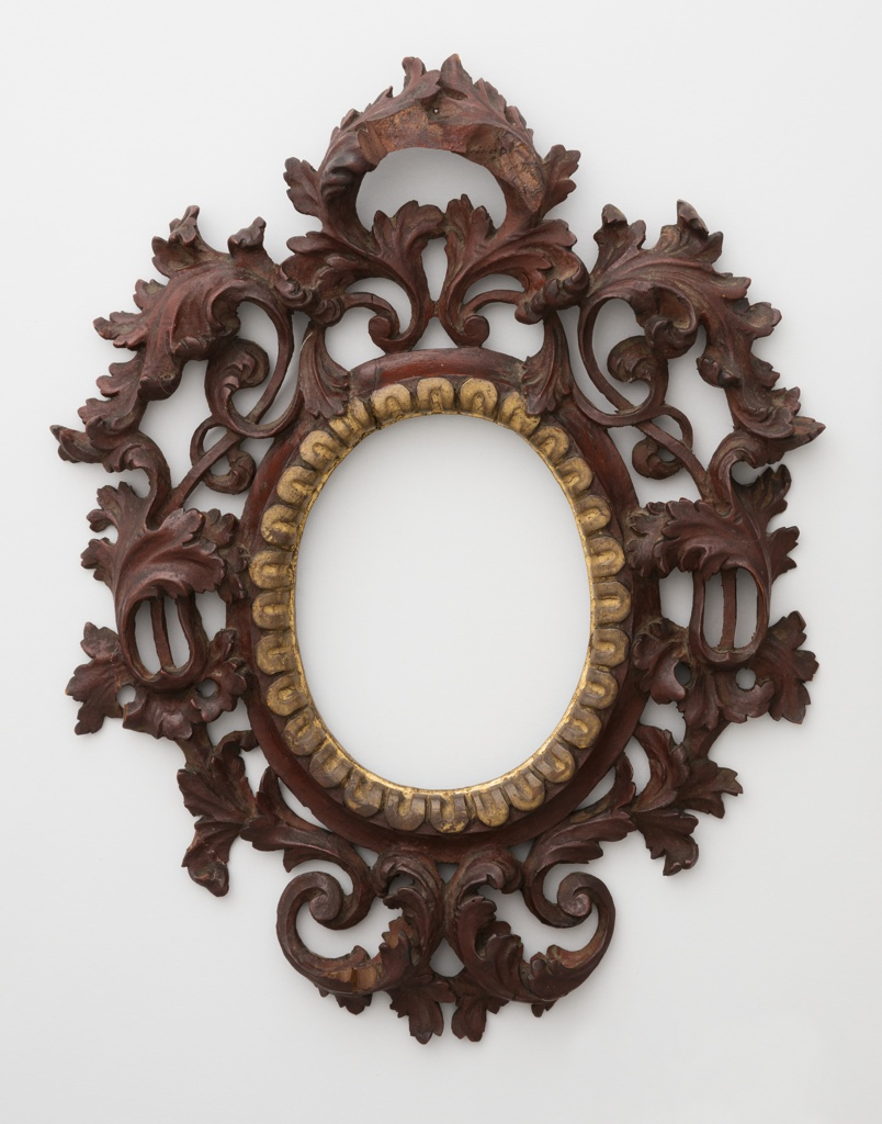 In late 17th-century/early 18th-century Venetian style, central vertically ovoidal moulded frame surrounded by acanthus branches; row of scallops decorates edge of opening.