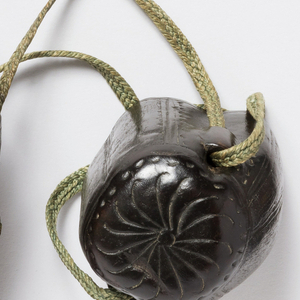 Irregular shaped tapering leather case, lid attached to body with a silk cord.