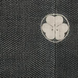 All over middle grey tone created by a tiny dot pattern created by a resist supplied through a stencil. Fabric dyed dark blue. A crest appears on each shoulder on the front and center of shoulders at back. Kimono is unlined and the fabric is double faced.