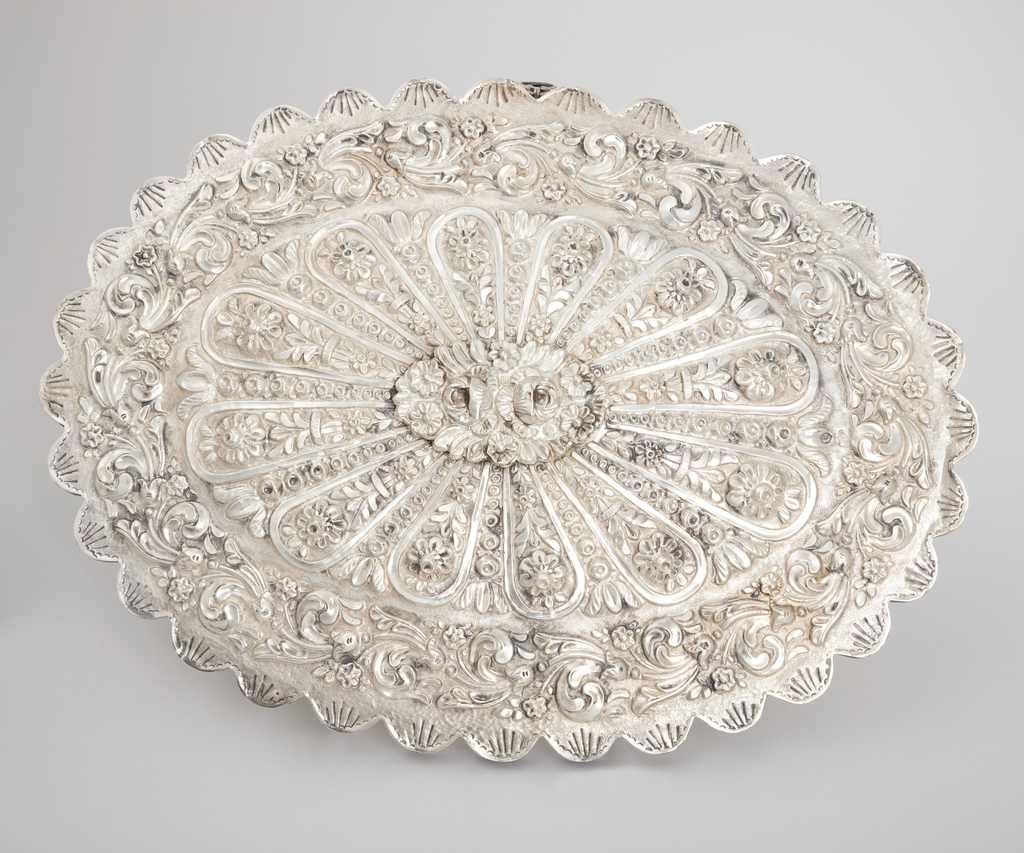 Scalloped oval silver frame, engraved with radiating lines, holding mirror glass. Back repousse with scrolled wreath around flowers in frames radiating from center, which is covered by a separate piece of oval repousse silver. Suspension ring on one long side.