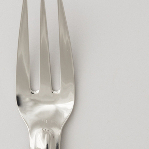 Formed as one piece of stainless steel. Blade with rounded tip, Three-tined with straight-sided handle slightly domed, elongated oval central section and rounded terminal.