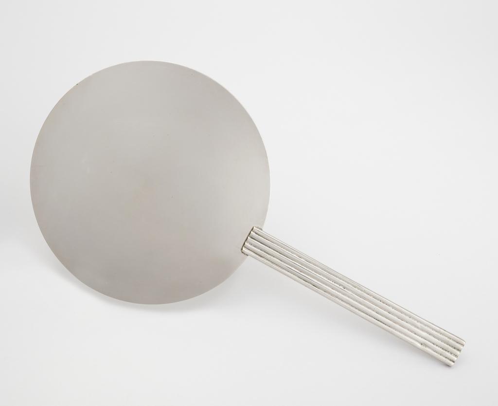 Flat, circular disc surmounting long, narrow rectangular and ribbed handle.
