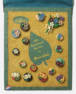 """Buttons on a board with a grass-like surface; at center, a space with writing: """"Old / Fashioned / Garden / by / Marion Weeber""""; upper left in oval: """"La Mode"""". 15 buttons shaped like bouquets on plates with handle (lids?) and one large bouquet at upper right. Trademark symbol of artist on left in shape of palette that reads: """"REGISTERED DESIGN / Marion Weeber / AMERICAN ARTIST""""."""