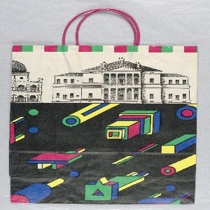 Shopping bag with a black and white classical building façade across the top. On the bottom, brightly-colored, three-dimensional, geometric shapes project diagonally against a black background.