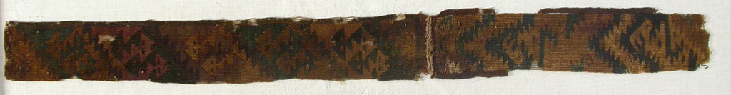 Narrow band in dark red, black and shades of brown and tan. Pattern shows intricate step design.