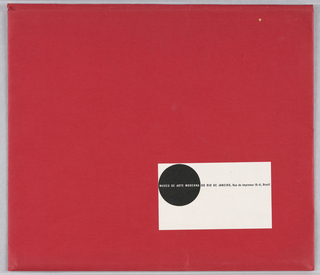 Horizontal rectangle format envelope. Red background with small horizontal white rectangle at lower right. Within rectangle, a black circle at upper left. Printed text in white at center of circle and in black within white rectangle lists museum name and address.