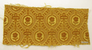 Gold velvet with a pattern of ribbon garlands and flower medallions.