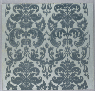 Two identical vertical symmetrical motifs side by side. Leaf and flower forms all in one shade of blue flock. The identical motifs meet at the center of the width of the paper and form subsidiary leaf and scroll motifs.