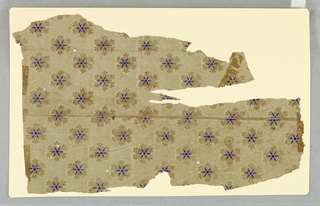 Stylized floral/snowflake design with blue center on cream ground.