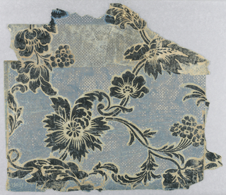 Two larger portions mounted on canvas, with space between, of serpentine vine design of large leaves set with large flowers and flower clusters; ground set with diagonal rows of dots and crosses.