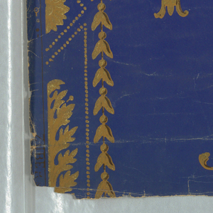 On lapis-blue ground, pattern of Arabesque-urns, garlands of bell flowers, beads and scrolls. Printed in mustard and metallic gold.