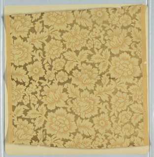 On patterned metallic gold ground, stylized tan flowers with gold and green accents in an all-over pattern.