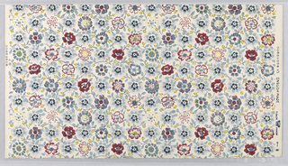 Small scale, all-over floral pattern with pin dot enframements. Red, blue and white flowers and yellow berries with blue leaves and tendrils on white ground.