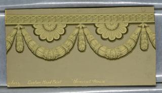 Design in classic style simulating architectural ornament and showing a horizontal band of curving reeded forms strung side by side on a rod, with leaf swags below enclosing half rosettes. Printed in cream, yellow, brown and black on a pink ground.