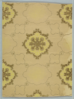 "On scroll-textured tan ground, ceiling paper features alternating green and gold medallions and ""outlined"" medallions connected to ""outlined"" floral forms."