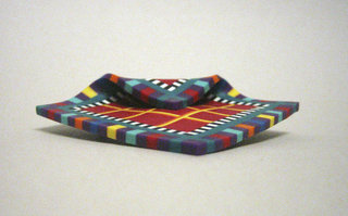Square flat shape with one edge folded over towards front. Brightly colored geometric pattern consisting of red and yellow grid, surrounded by frames of black and white, and of polychrome squares, all produced in colored-body marquetry technique. Metal safety clasp attached to back.
