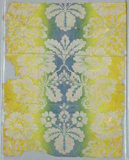 Vertically striped ground of blue to green to yellow, with over-printed symmetrical pattern of flowers on curving branches, diagonally striped with white. Ombre, also called irise or rainbow paper.