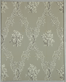 """Against a gray ground are printed widely spaced, diagonally running strips of openwork grill with twisting vines and blossoms. Diamond shaped areas formed by intersecting diagonals enclose a single bouquet of blossoms and foliage. Printed in dark gray and white. b) Same as """"a"""" but larger sample."""