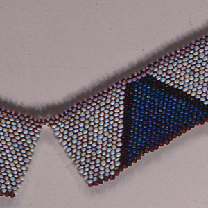 Necklace composed of four rectangular panels. Each has a white field with a blue triangle bordered in black. The upper edge is pink and the lower edge of each rectangle is red. Fastened with cone-shaped metal buttons.