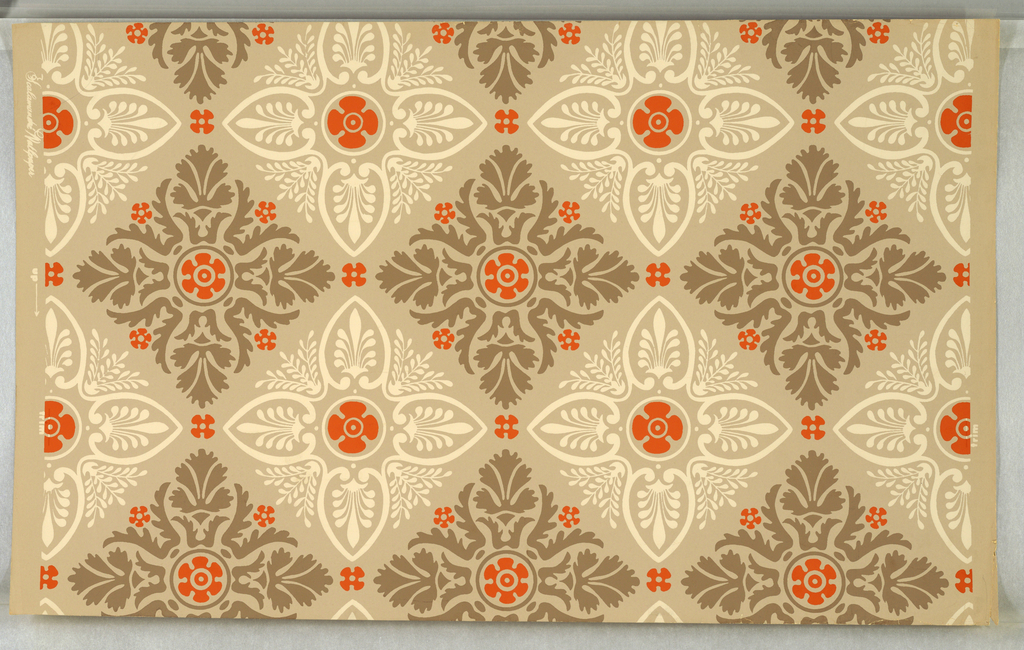 "On putty-colored ground, stylized symmetrical leaf and flower patterns in alternating brown and white groupings, conforming to diamond configuration with bright orange rosettes in centers and around edges of each grouping. Printed in margin: ""trim."""