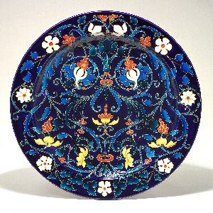 Circular in form, with flat rim, concave center; dark blue background, turquoise blue leafy scrolls with white, yellow, orange flowers; right and left sides mirror image.  Glaze colors contained in cloisonne-like channels.  Back glazed mottled greens; high circular foot unglazed.