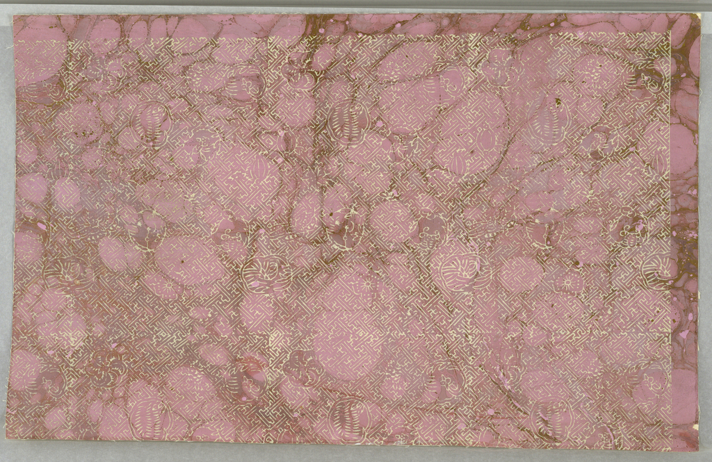 """White fret-work interspersed with white fruits and flowers irregularly spaced. All are in outline against a """"tortoise shell"""" ground of lavender and gold. A non-repeating """"Chinese Tea Chest"""" paper."""