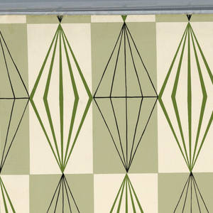 """Pale green vertical rectangles alternate with white vertical rectangles in checker board fashion as a background. Prismatic """"diamonds"""" outlined in green are printed against the white rectangles, while slightly different """"diamonds"""" of the same size are outlined in black and printed against the green rectangles. From Shumacher's """"Crystal"""" collection."""
