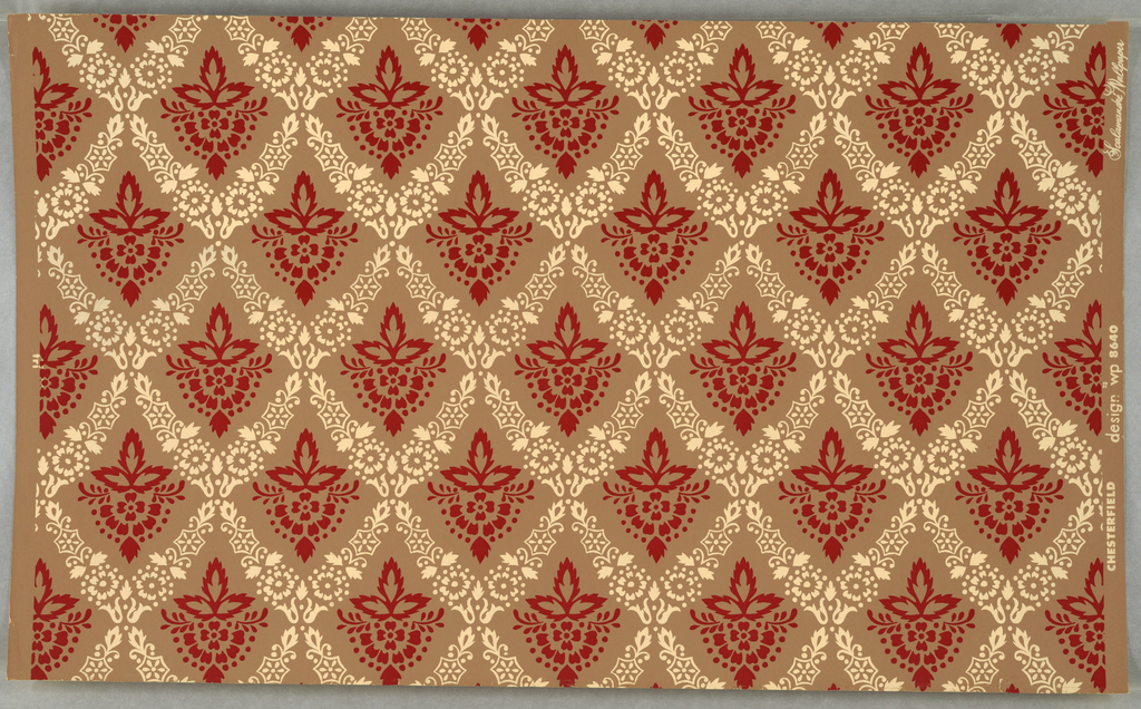 "On light brown ground, small repeating stencil-like pattern: diamond-diaper formed by beige flower forms, scrolls, etc. with red flower centered in each opening. Printed in margin: ""Chesterfield Design wp8640 Scalamandre Wallpaper."""