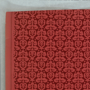 All-over pattern of tiny stylized flower and stalk, printed in deep red on red ingrain paper.