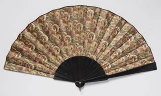 Folding fan with Aesthetic Movement style printed cotton leaf depicting eight different overlapping designs for ceramic plates of the period surrounded by a small fish scale pattern. The reverse leaf is dyed and glazed dark brown cottton. The sticks and guards are made of wood ebonized black with unpainted wood slips in between the two layers of the leaf. At the edge of the fan, binding the two layers together, is a narrow woven binding tape that is dyed black. At the rivet there is a bone washer and metal loop.