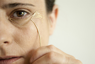 "a chevron shape conforming to the undereye area of gold-plated brass with flowing  ""wrinkles"" off the outer edge,with a cheek-formed line descending from the undereye"