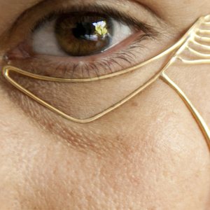 """a chevron shape conforming to the undereye area of gold-plated brass with flowing  """"wrinkles"""" off the outer edge,with a cheek-formed line descending from the undereye"""