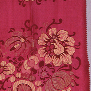Crimson crepe ground with large-scale highly conventionalized blossoms grouped in horizontal repeat. Foliage in satin weave. Flowers in supplementary weft of yellow and beige silk.