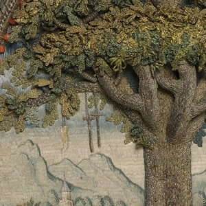 Small panel of embroidery in high relief of a tree in an oval with an elaborate framework.  The field is filled by an oak tree with dimensional leaves in shades of green. The trunk and branches are very dimensional, and are worked in silver metallic thread, now tarnished. At the base of the tree is a salamander, also in silver metallic thread. The background shows a landscape worked in pale silks with mountains and buildings, possibly a monastery. From the limbs of the tree hang crutches, a wax leg, and a censer. 