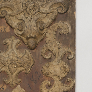 Fourteen tall, rectangular wood panels mounted with molded asphaltum samples of wall and ceiling ornaments in various motifs ranging from bead-and-reel and arabesque borders to foliate forms, shells and cornucopia, to animal and figural forms.
