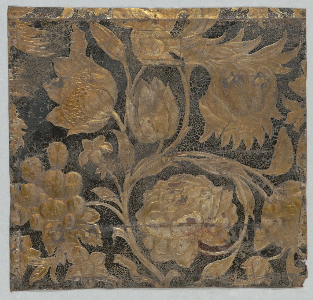Large-scale sunflowers and rose, with a bunch of grapes. Gilded and embossed.